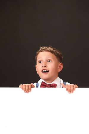 Surprisingly happy child with huge eyes. white and black space for text. emotional boy with a poster. share the good news. awe of seeing a cry of joy. Фото со стока