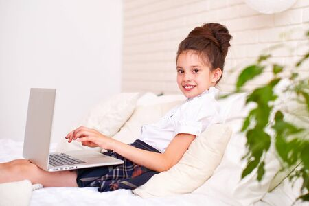 the child is happy to communicate with friends via the Internet .home schooling, search and study, new knowledge.happy baby on the bed with the computer. little student girl lying on the bed smiling.