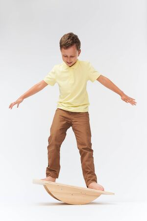 baby boy stands on a special simulator for training the vestibular apparatus. to keep the balance standing on the treadmill. training of the vestibular apparatus.balance exercise balancing Imagens - 127506783