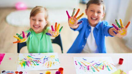 lustige kinder zeigen ihren handflächen die gemalte farbe. Kreativkurse Bildende Kunst. zwei Kinder, ein Junge und ein Mädchen lachen. selektive Fokussierung auf die Handfläche. glückliche Kinder in der Zeichenschule