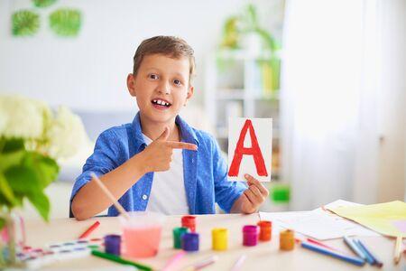 chłopiec odrabia lekcje w domu. szczęśliwe dziecko przy stole z przyborami szkolnymi uśmiecha się śmiesznie i w zabawny sposób uczy się alfabetu.pozytywny uczeń w jasnym pokoju z namalowanymi literami w dłoniach Zdjęcie Seryjne