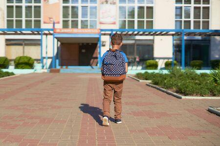 das Kind geht zur Schule. Junge Schuljunge geht morgens zur Schule. glückliches Kind mit einer Aktentasche auf dem Rücken. freier text, kopierraum. Blick von hinten auf das ausgehende Kind Standard-Bild
