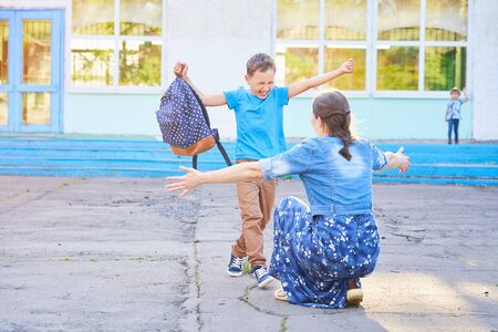 mom meets her son from elementary school. joyful child runs into the arms of his mother. a happy schoolboy runs towards his mother holding a school bag in his hands. the end of the school day Banco de Imagens