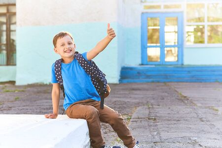 the child goes to school. the boy in the morning, goes to school. portrait of a happy child with a briefcase on his back. concept student goes to school and waving goodbye. free text, copy space.