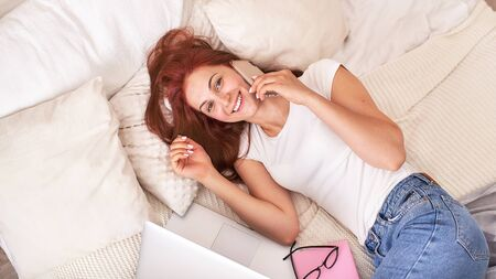 beautiful young girl smiling with phone and laptop on the bed. communication is fun and interesting Internet and laptop. positive red haired girl in a bright t-shirt and jeans 版權商用圖片