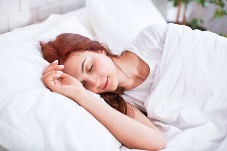red-haired beautiful girl sleeps with both hands under her head on a pillow in a light bed in the bedroom. sweet girl sleeping bedroom in the morning light.