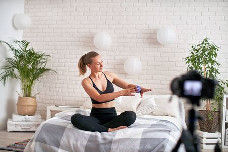 online stream coach shows technique exercise massage ball. relaxation of the muscles of the hand with a massage ball. in a modern home environment, the girl writes a video blog self massage Banco de Imagens