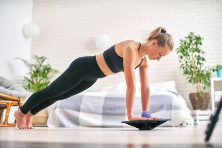 woman doing exercise on a special simulator balancer. blonde athletic sportswear, home did exercise strengthens the muscles. the girl keeps her balance balancing on the sports equipment.copy space. Banco de Imagens