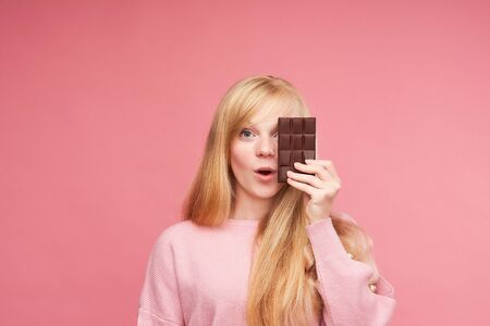 Young beautiful blonde with chocolate. teen girl bites chocolate. the temptation to eat forbidden chocolate. cheerful positive young girl holding a chocolate bar. Studio, pink background. copy space