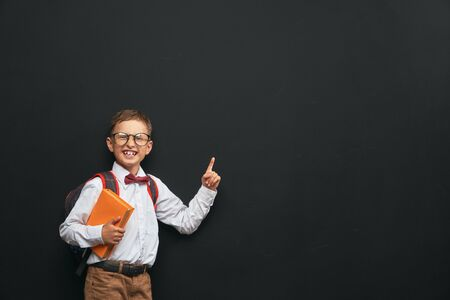 joyful little boy with glasses, with a briefcase standing on a black background with a book in his hands. happy child the student pointing to the top, wascosa. free text, copy space