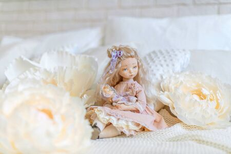 two dolls made by hands from textiles are very similar to living people. designer dolls. sitting on the bed. creating dolls for the new year holiday.doll mom with a little baby. mother's daughter game 免版税图像