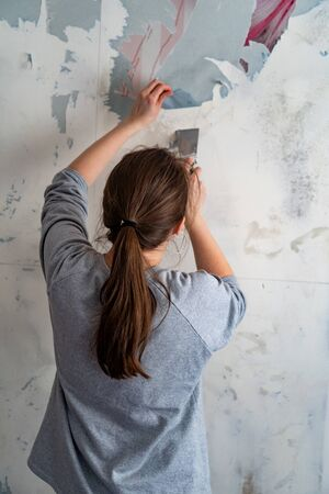 woman removes scraps of old Wallpaper from the wall with a spatula. Repair of premises. Removing wet Wallpaper. Deleting Wall paper
