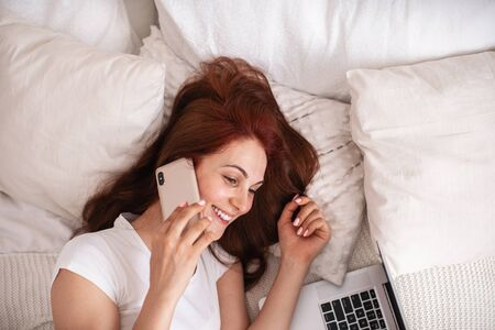 Happy young woman lying on a bed and talking on a mobile phone. The girl smiles, a notebook and a laptop are lying next to her. She works from home. Freelance. Self-isolation of the house. Close up