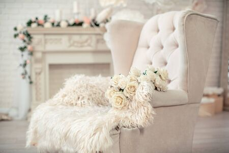 modern white chair in English style in a bright room with a fireplace decorated with flowers. In a room with indoor plants. On the chair is a natural skin and a bouquet of white roses. Copy space