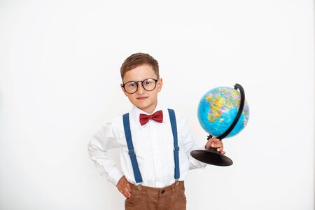 Portrait of a cute little schoolboy in a school suit with suspenders and glasses isolated on a white background, holding globe. The child is studying geography. Cute boy is traveling. Back to school.