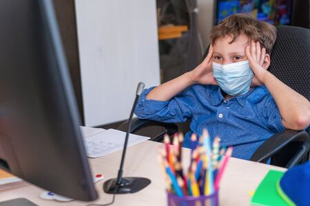 boy with mask on his face is tired distance learning during quarantine covid-19. concept of online education. Social distance, self- isolation. Distance learning due to virus, flu, epidemic,pandemic.