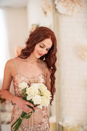 beautiful young woman with a bouquet of white roses in a bright interior looks at the flowers. A pretty girl with curly red hair in a gold dress with flowers in her hands, smiling. spring holiday