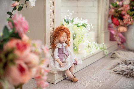 interior design doll with a human face , made by hand from textiles, in a retro style , sits on the fireplace decorated with flowers. creating dolls for the holiday. The doll companion 免版税图像