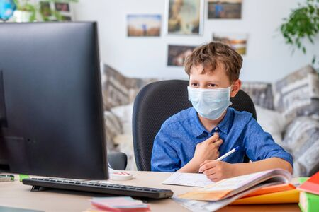 Boy in face mask with computer does his homework during a coronavirus quarantine. concept of online education. Social distance, self- isolation. Distance learning due to virus, flu, epidemic COVID-19 免版税图像