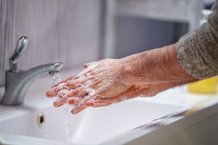 man washes his hands with soap at home . The concept of virus protection. hand hygiene. Fight against microbes, viruses, bacteria, covid-19. Stay at home. Quarantine. World pandemic.