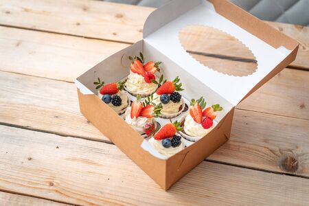 Fresh and delicious cupcakes with yogurt cream and fresh berries. Cakes with cream, strawberries, blueberries, blackberries and raspberries Packed in boxes. delicious sweetness. Beautiful pastries.