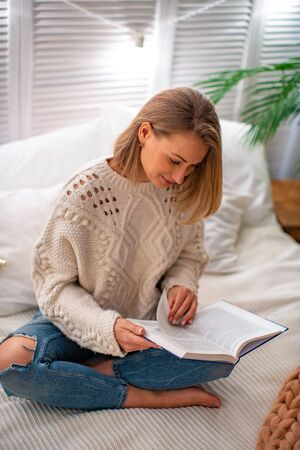 young smiling woman is sitting on the bed with a book. The blonde spends time studying educational literature. The evening reading. The concept of leisure. Stay at home
