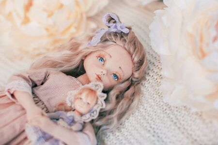 Designer interior doll with a human face, made by hand from textiles, in retro style, lying on a knitted blanket surrounded by flowers creating dolls for the holiday. Companion doll 免版税图像
