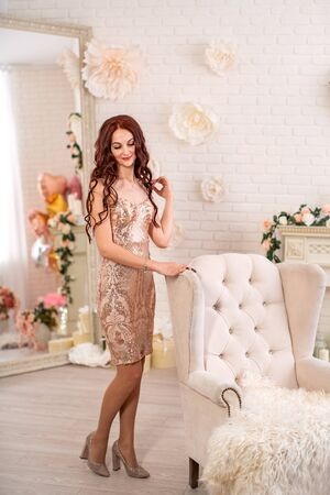 An attractive young woman in a gold dress stands next to a chair in a delicate floral interior. A pretty girl with curly red hair, in a beautiful dress, in a floral interior, smiles. spring holiday