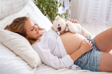 Pregnant woman is lying on the bed on her back. Stroking her bare belly. Expectant mother in cozy bright room.Rest and communication with the unborn baby. concept of waiting. Preparing for childbirth.