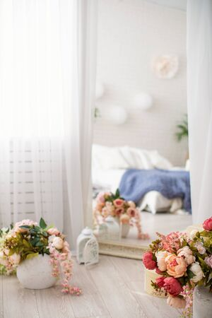 High mirror, in chic frame, draped in white tulle, next to vases with flowers. Reflection of bright bedroom. large bed with white linens and knitted blankets. concept of home comfort and recreation.