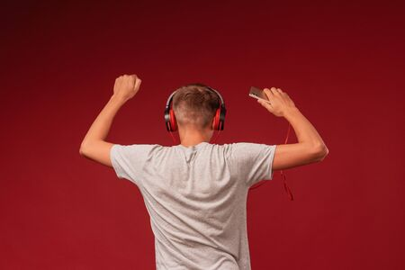 a positive teenage guy with headphones, listening to music from his smartphone on a red background, dancing with his hands up, turning his back. Rear view.