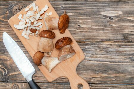 group delicious white mushrooms on wooden table, partially chopped. natural mushroom from forest. vegetarian food ingredients. porcini mushrooms and knife on wooden board view from top. daylight.