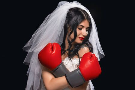 portrait of an attractive brunette with red lipstick, in a wedding dress, veil and Boxing gloves. young girl in the role of a bride on black background, arms crossed, protects herself and looks away. Stock fotó
