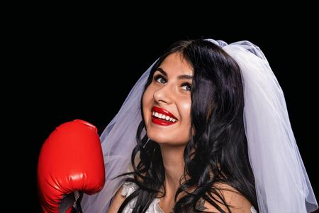 portrait of an attractive brunette with red lipstick, in a wedding dress, veil and Boxing gloves. Close-up of a fat girl in the role of a bride on a black background, smiling and looking up.