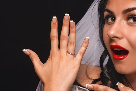 Close-up of an attractive bride, in a veil and wedding dress, showing her hand with an engagement ring, on a black background. The brunette shows off the ring with delight. The concept engagement.