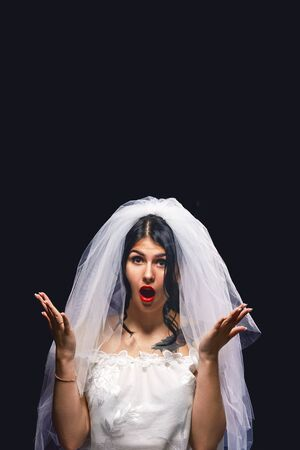 woman dressed as a bride throws a bouquet up on a black background. The brunette is very surprised that the bouquet falls on her head. Concept of wedding customs. 免版税图像