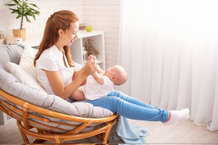 Happy loving family. young mother is sitting on an easy armchair with small child. woman smiles, plays and hugs baby. the concept motherhood. Mom spends fun gymnastics with her newborn daughter.