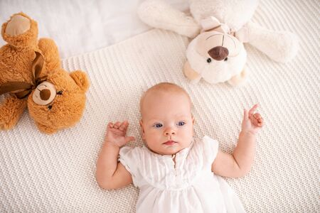 Cute little girl with blue eyes 4 months old lies on bed with Teddy bears and looks away. small curious funny baby in light clothes, watching what is happening, looking away. The view from the top.