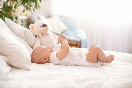 Cute 4 month old baby is lying on his back on the bed and playing with his hands. A bed with light linens, blankets and pillows, and a Teddy bear sitting next to it. The room is cozy and bright.