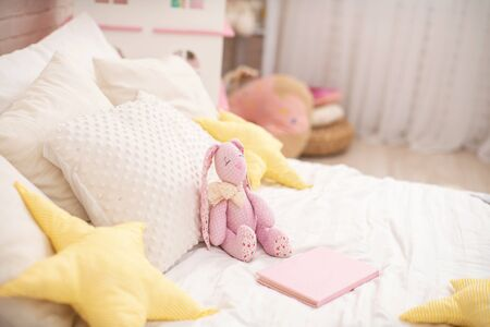 Handmade plush rabbit made of fabric sits on a cozy bed in the children 's room. Nursery there is a Dollhouse and a lot of toys. On the bed there are a lot of soft pillows stars. copy space. 免版税图像 - 145937356