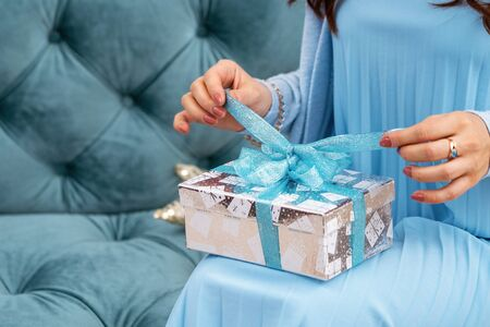 Close-up hands of woman opening gift box on holiday, waiting for desired. Pulling ribbon and untying bow on box. A woman is sitting on a turquoise banquette with a carriage tie in a blue outfit.