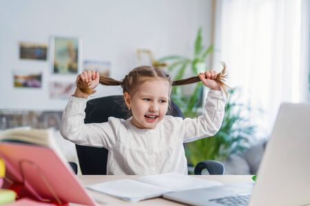 little cheerful girl uses laptop to study at home. child laughs and fools around, tired of distance learning. digital concept e-learning, during epidemic, quarantine and self-isolation. Problems.