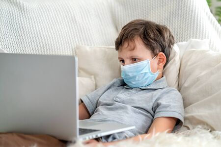 Focused boy in a mask, lying on the couch with a laptop during the quarantine period. He does not go to school, is in isolation, on distance learning. Stay at home, e-learning. Stock fotó