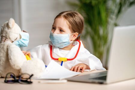charming little girl in a white coat and mask, using a stethoscope, listens to Teddy bear. Cute little preschooler in uniform playing game of doctor patient in clinic, concept of children's health Stock fotó