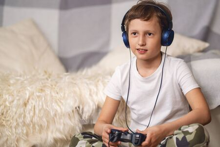 Cheerful boy in headphones, with joystick in his hands, playing video games. Child has fun activities in period self-isolation, during an outbreak of coronavirus. Concept virtual and computer games.