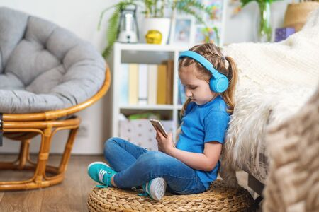 Cute little girl listening to music in headphones on smartphone. Stay at home. child is sitting with mobile phone in his hands and enjoys listening to his favorite songs. Dependence on gadgets. Copy space. Stock fotó
