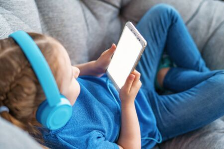 little girl with headphones and holding smartphone white screen in her hands is lying on sofa and looking at mobile phone screen. Close up. Selective focus on hand. Concept leisure during quarantine