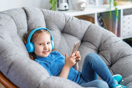 little girl with headphones and holding smartphone in her hands lies on large round armchair and looks at screen frame and smiles listens to music. Side view leisure Concept during covid-19 quarantine Stock fotó