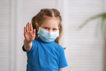 A little girl in a medical mask looks at the camera and makes a stop gesture during the coronavirus pandemic on a light background. The child puts his hand forward to determine the social distance. Stock fotó
