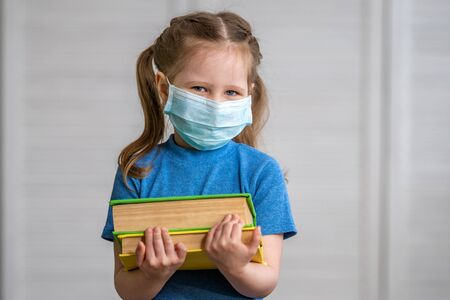 Little girl in a medical mask with a book in her hands on a light background. Education concept with copy space. during quarantine and self- isolation. e-learning due to Covid-19 coronavirus pandemic. Stock fotó